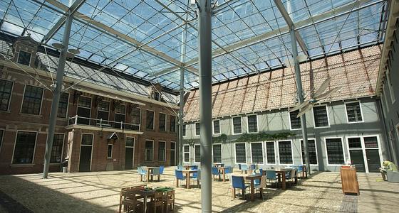 De binnenplaats van het museum met glazen daak en terras