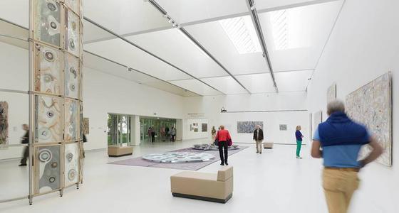 Een grote lichte zaal met witte muren, plafond en vloeren waar kunst tegen de wanden staat en hangt maar ook midden inde ruimte. Een aantal bezoekers bekijkt de kunst in de ruimte.