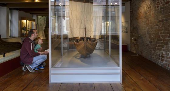 Een man en kleine jongen zitten op hun hurken voor een grote vitrine en kijken naar het houten zeilschip met uitgevouwen zeilen die hierin is opgesteld