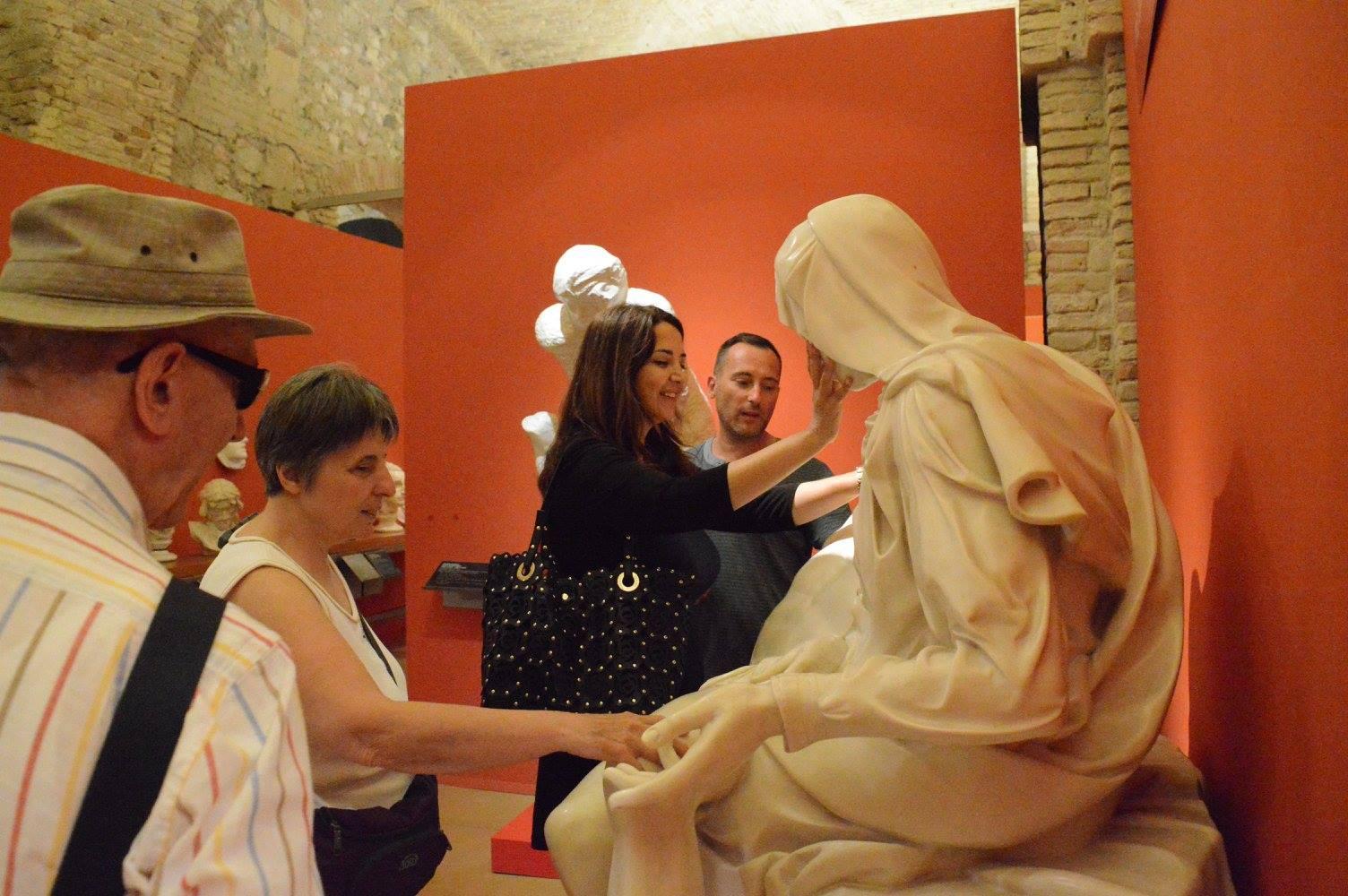 mensen voelen aan een wat stenen beeld van een vrouw die in kleermakerszit zit. Ze draagt een hoofddoek.