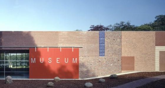 De stenen entreemuur van het museum met daarop een groot roodvlak met de tekst museum in witte letters