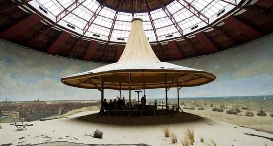 In de ronde ruimte met glazen dak staat in het midden het bezoekersplateau omgeven door nagebootste duinen die overgaan in de rondom liggende schildering op de wand.