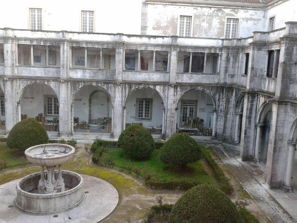 Een wit vervallen oud gebouw met groene binnentuin. De muren en pilaren van de galerij zien er verweerd uit, evenals de fontein op de binnenplaats