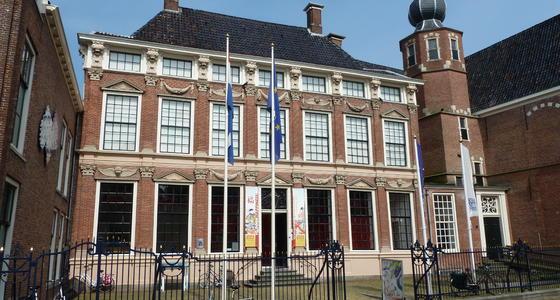 Een statig aandoend gebouw van rood baksteen met grote ramen en een grijs pannendak. Voor het plein voor het gebouw staat een hoog zwart spijlen hek