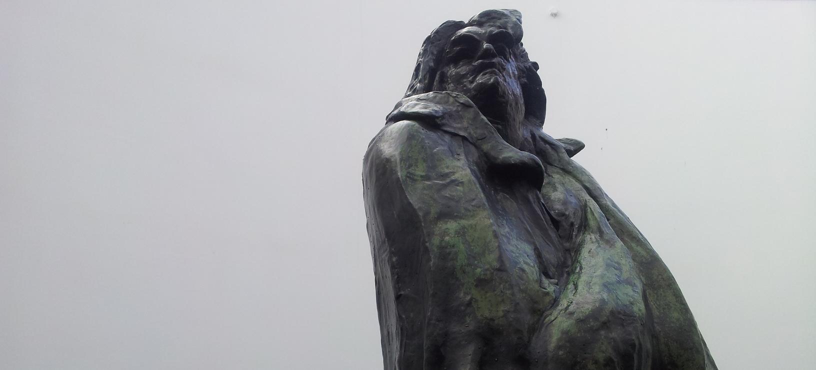 Bovenkant van het beeld van Balzac, een bronzen beeld van een man met halflang haar en een baard en een dikke jas met grote revers aan