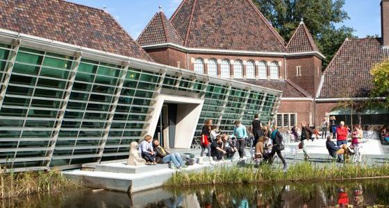 De entree van het museum met glazen pui en stenen trappen met daarop mensen die genieten van het zonnetje.