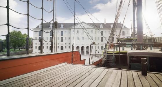 Vanaf een boot is tussen het tuig van de zeilen en de klimtouwen door het museum te zien. Een groot wit statig gebouw