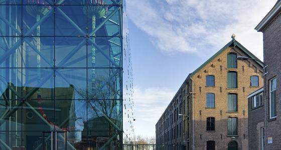 Links een pui van een glazen gebouw en rechts een stenen gebouw van lichtbruine bakstenen. Het bakstenen gebouw weerspiegelt in de glazen pui