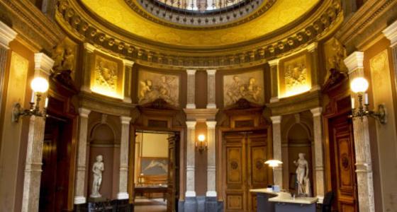 Een aangezicht van een ronde goudkleurige ruimte met marmeren zuilen en beelden in de nissen.