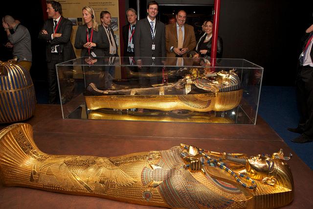 Mensen staan te kijken naar wee gouden sarcofagen op een houten podium