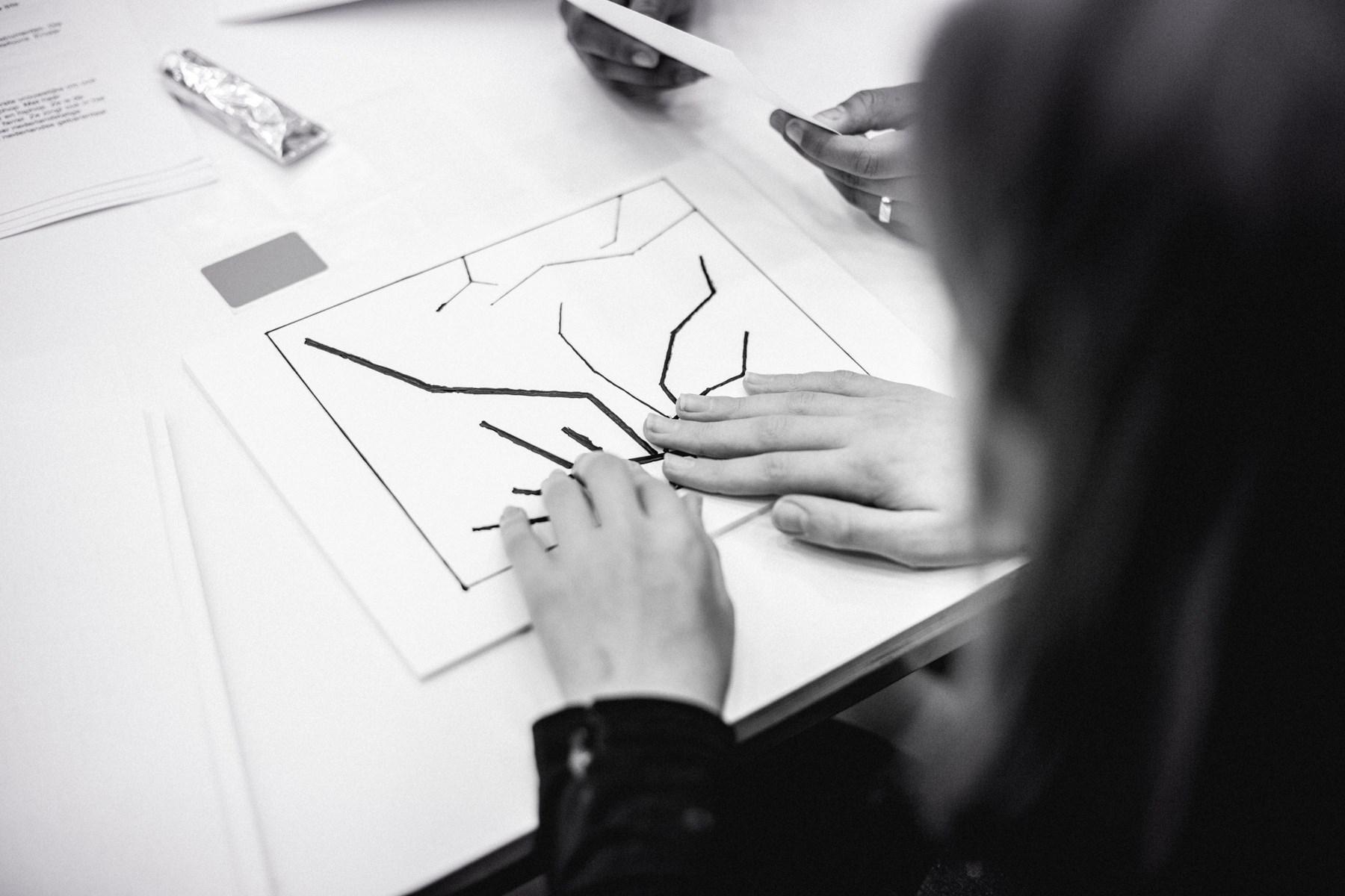 Een zwart wit foto van handen die aan een tactiele tekening voelen