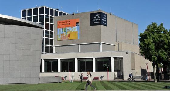 Het betonnen gebouw dat bestaat uit een aantal vierkante blokken tegen elkaar met op de hoek van het voorste blok een zwart bord met de tekst Van Gogh museum