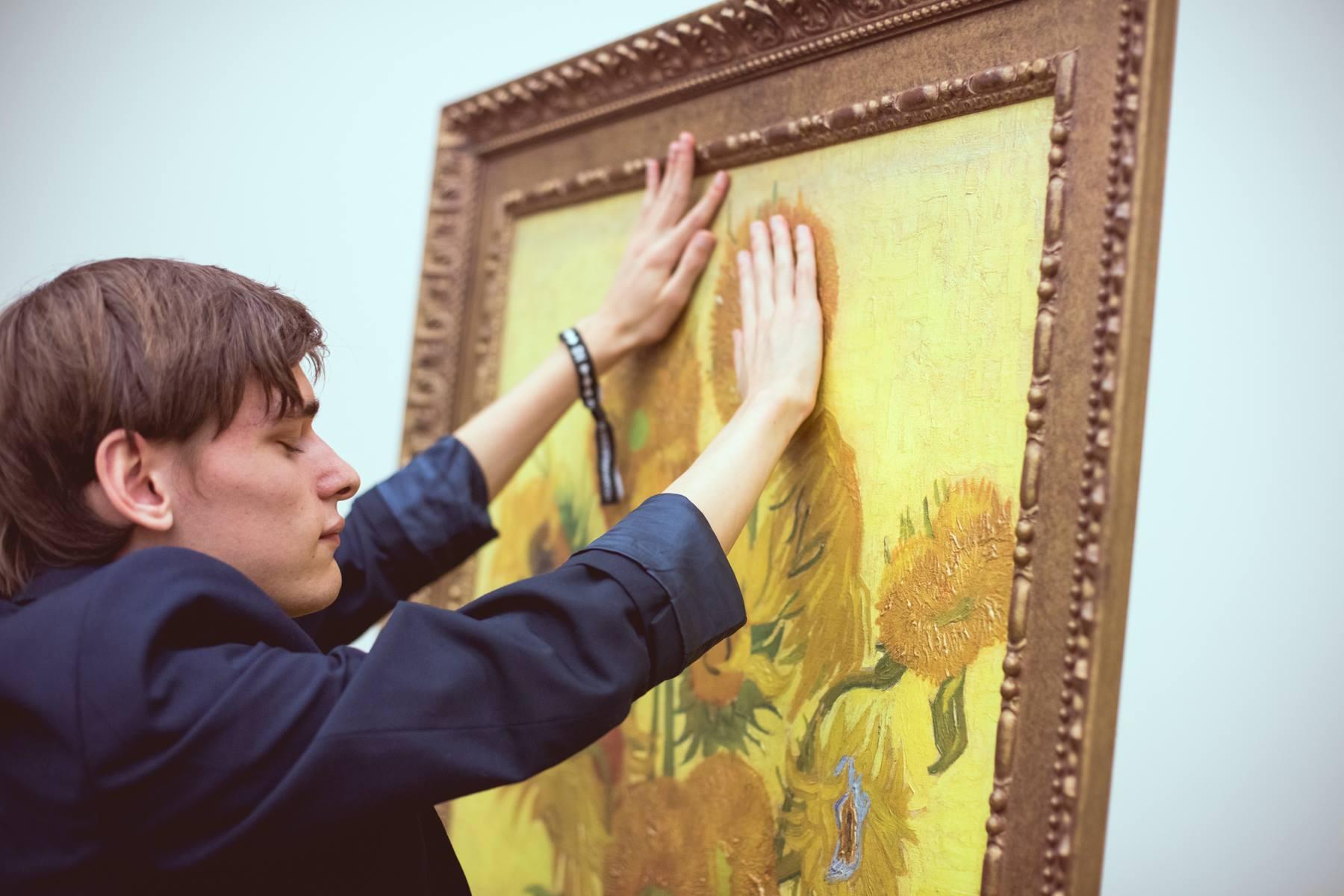 Een man voelt met twee handen aan een levensgroot schilderij van Van Gogh; de beroemde zonnebloemen.