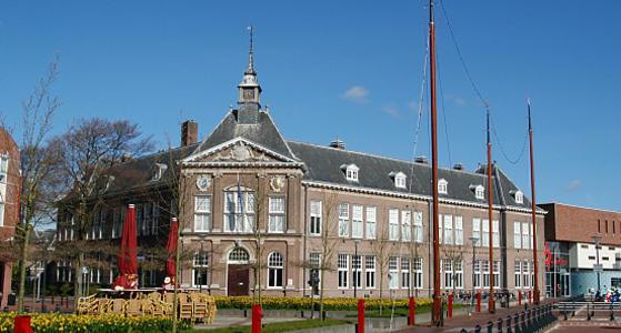 Een statig gebouw van rode bakstenen met een grijs pannen dak. De hoek van het pand heeft een torentje en op het dak staan kleine dakkappellen.