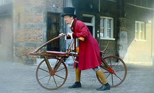 Een foto van een man in lange rode jas en hoge zwarte hoed die een oudewetse houten fiets naast zich voortduwt over de grijzen klinkerstraat