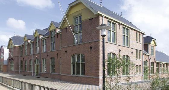 Een rood bakstenen statig gebouw met twee verdiepingen omringd door een heuphoog hek