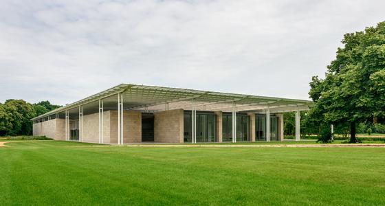 Een modern gelijkvloers gebouw met licht bruine stenen muren en een ingenieus dak voor de beste lichtval naar binnen staat op een groen vlak grasveld