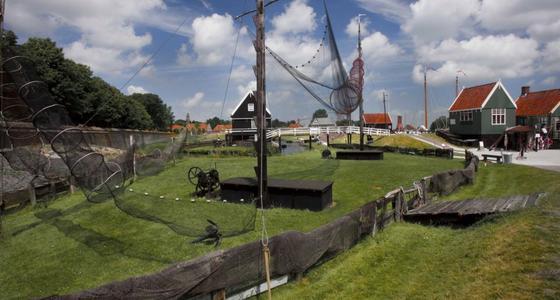 Een omheind grasveld met uitgestalde vissersnetten. op de achtergrond houtenhuisjes en een witte houten gebogen brug.