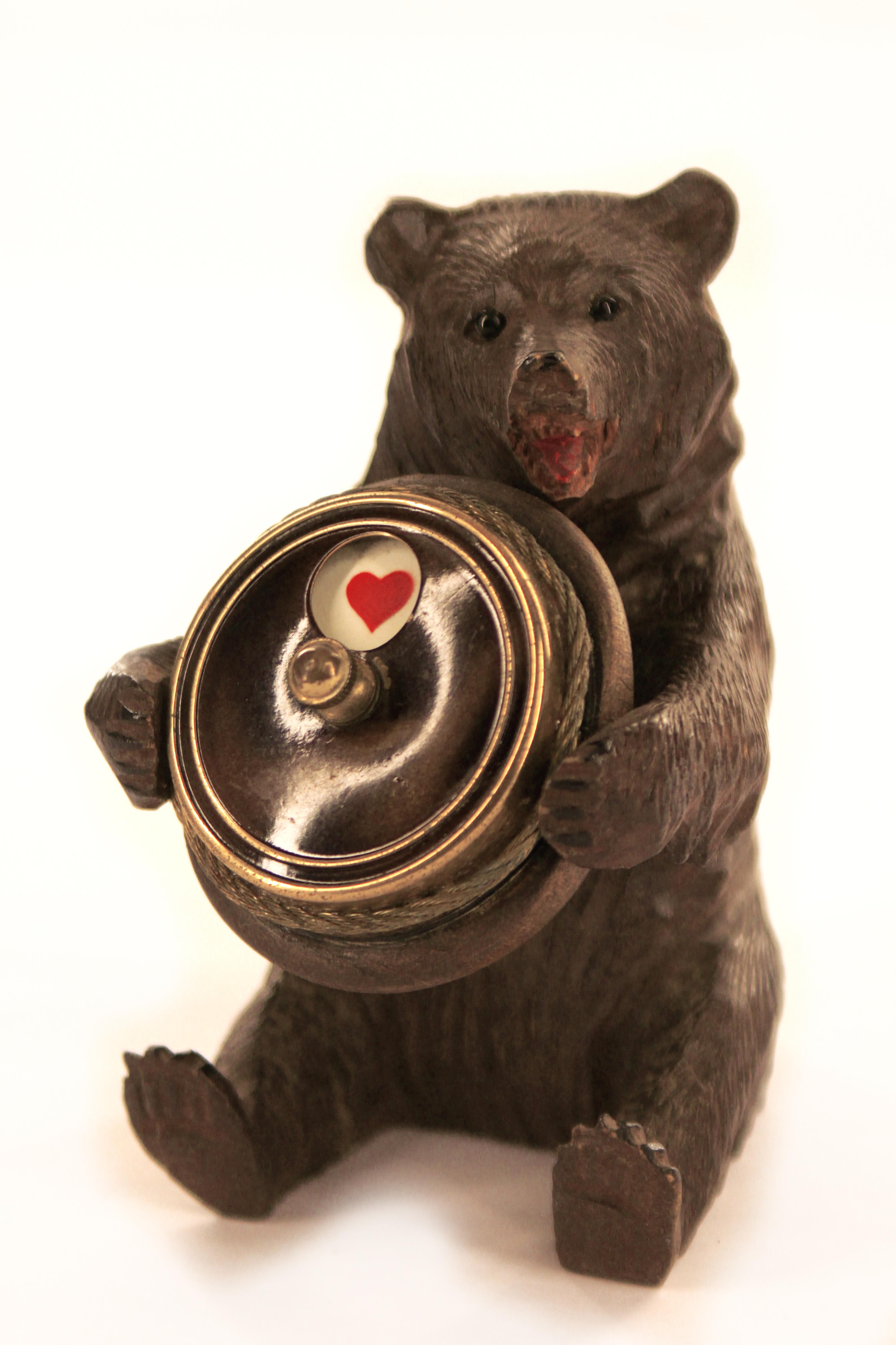 Een foto van een beeldje van een beer, zittend op zijn kont. De Beer heeft een rond voorwerp in zijn poten met daarop een hartje, een van de symbolen van een kaartspel