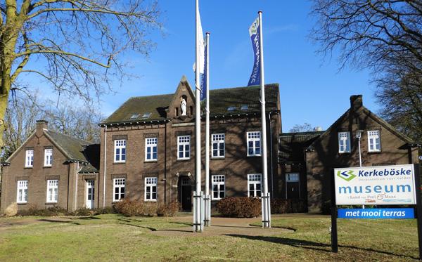 Een statig tweeverdiepingen hoog gebouw van bruine bakstenen en een grijs pannendak. Het gebouw is symetrisch met aan beide zijde van de ingang 2 ramen naast en boven elkaar. Voor het gebouw licht een grasveld met daarin twee hoge vlaggenmasten.