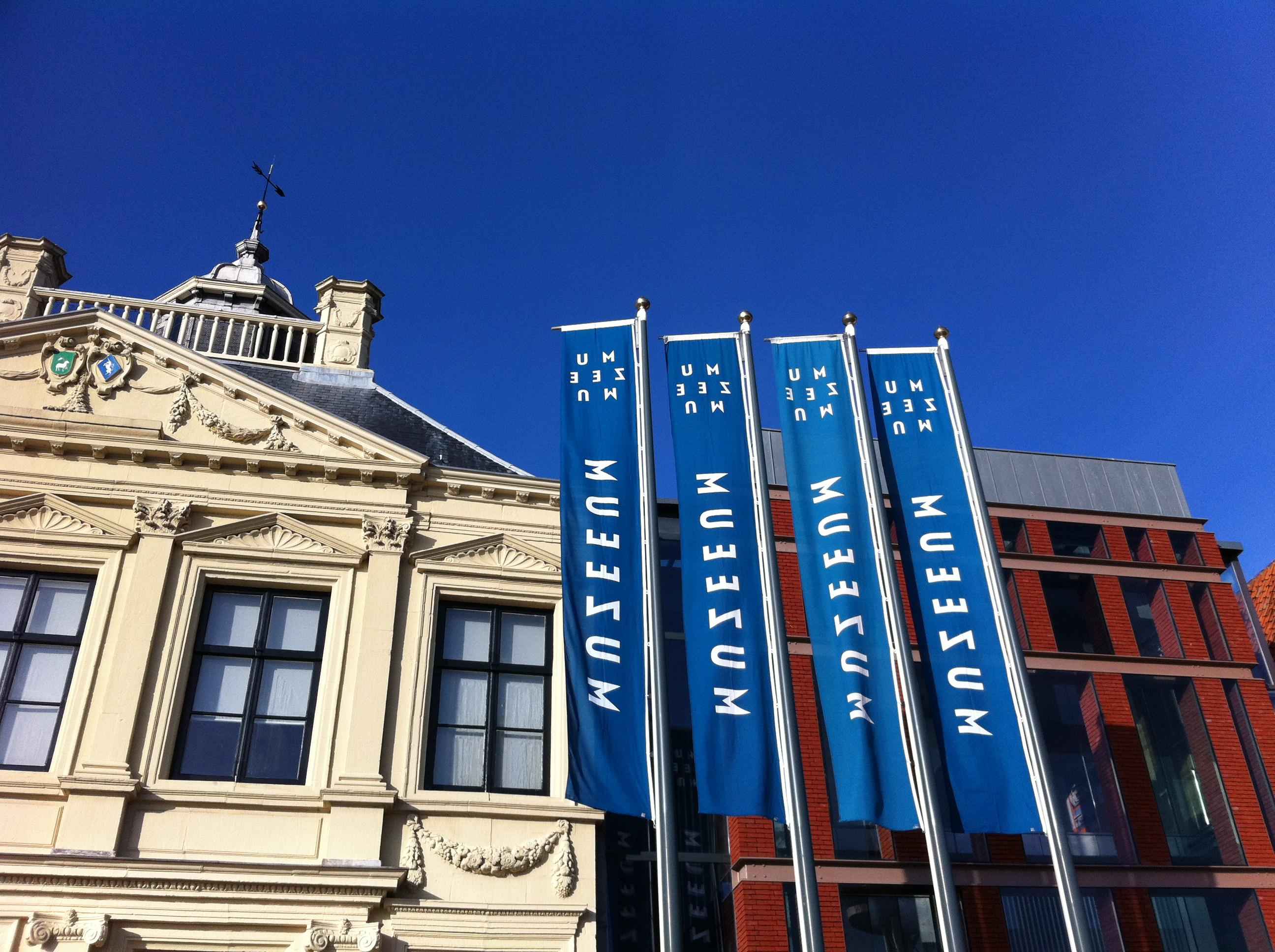 De gevel van een statig cremekleurig gebouw naast een donkerrood modern bakstenen gebouw. Voor de gebouwen 4 vlaggenmasten met blauwe banners met daarop in witte letters de naam van het museum MuZEEum