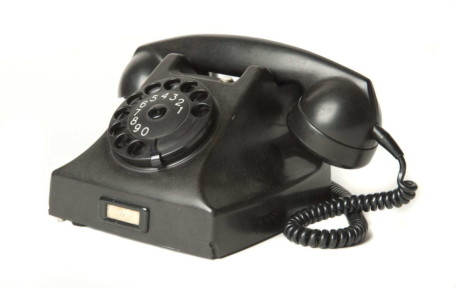 Een ouderwetse zwarte bakeliet telefoon met ronde draaischijf en afneembare hoorn met gekruld snoer.