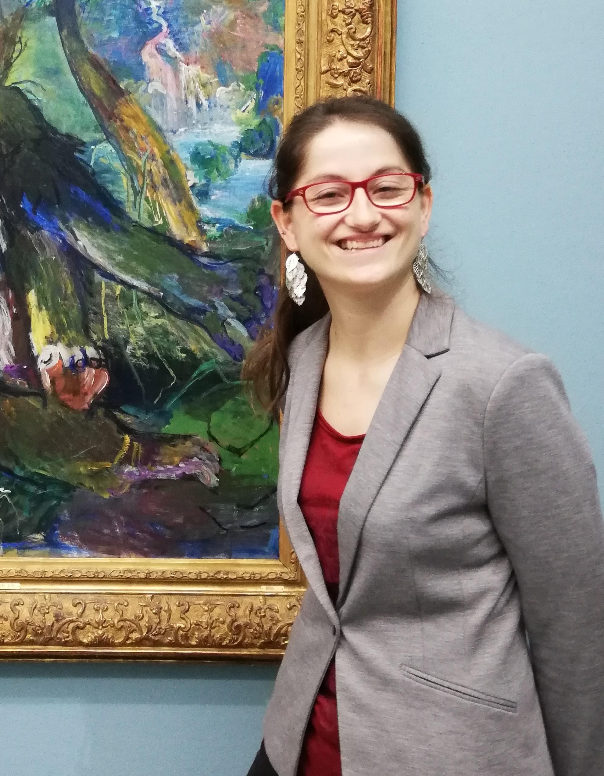 Met een brede glimlach staat Kachiri voor een schilderij. Haar donkerbruine lange haar zit in een staart en op haar neus staat een rode bril. deze past mooi bij haar rode shirt onder grijzen colbair