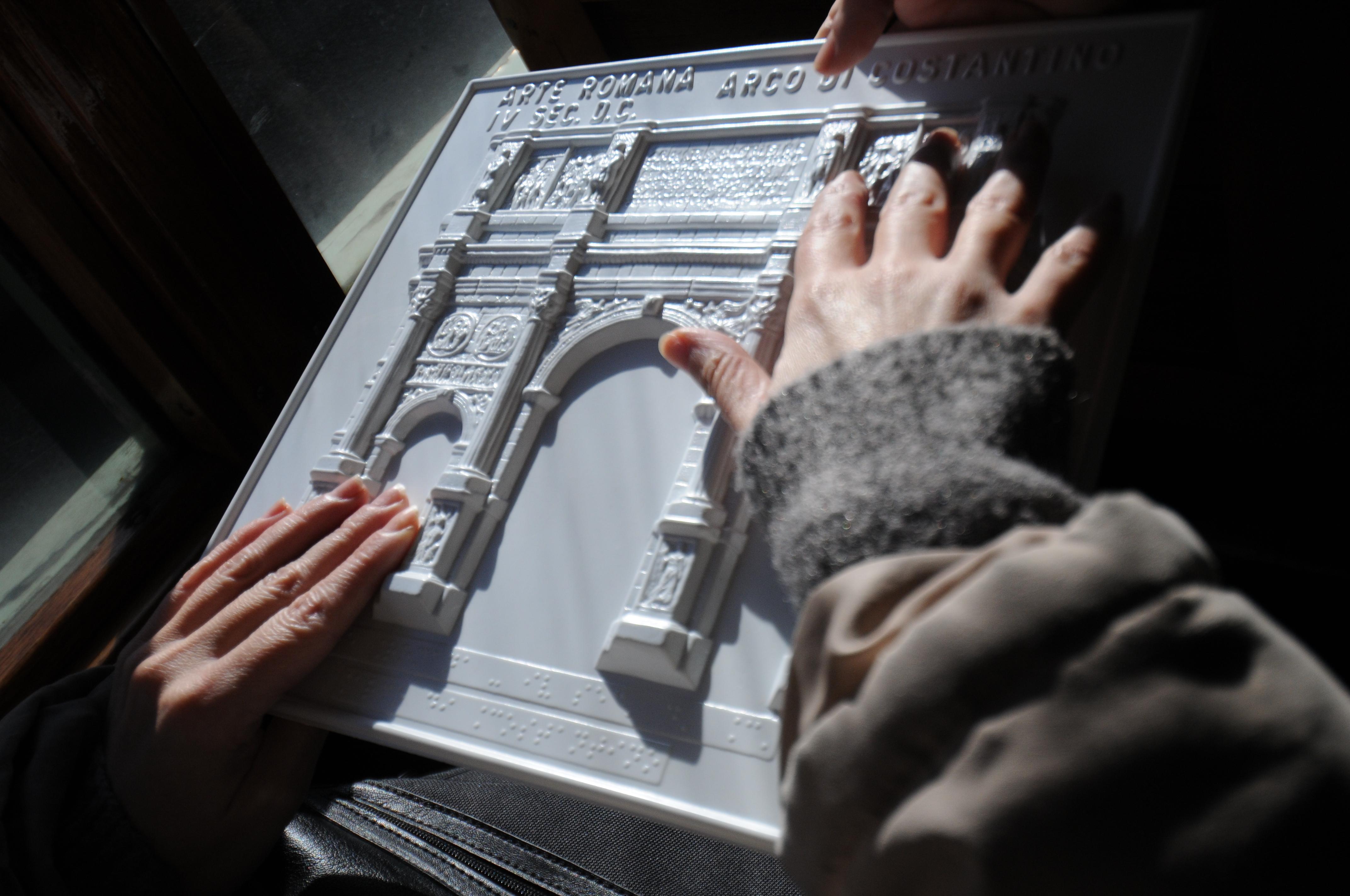 twee handen voelen aan een driedimensionale weergave van een architectonisch gebouw. Een Arque the triomphe boog