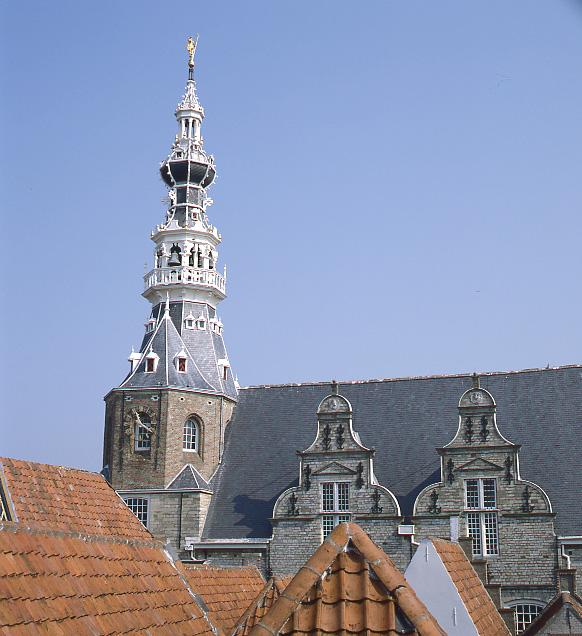 Achter de rode pannendaken, steekt het grijze dak met imposante toren van het stadhuis af tegen de blauwe lucht. Het dak van de toren is opgebouwd ui verschillende lagen met witte balkonnetjes en loopt uit in een punt. De dakkapellen op het dak hebben sierlijke klokgevels.