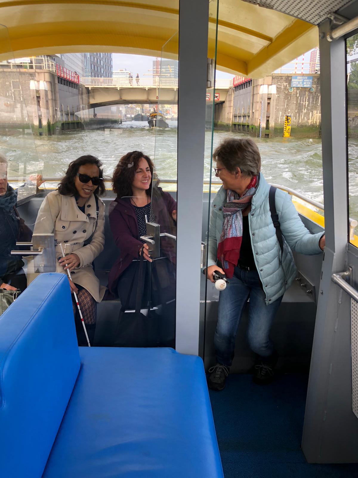 3 dames zittend op het achterdek van de watertaxi met de Leuvenhaven op de achtergrond