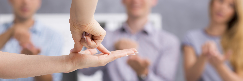 Een foto met op de voorgrond een platte linkerhand met daarop de duim en wijsvinger van de rechterhand die een tentje vormen op de platte hand