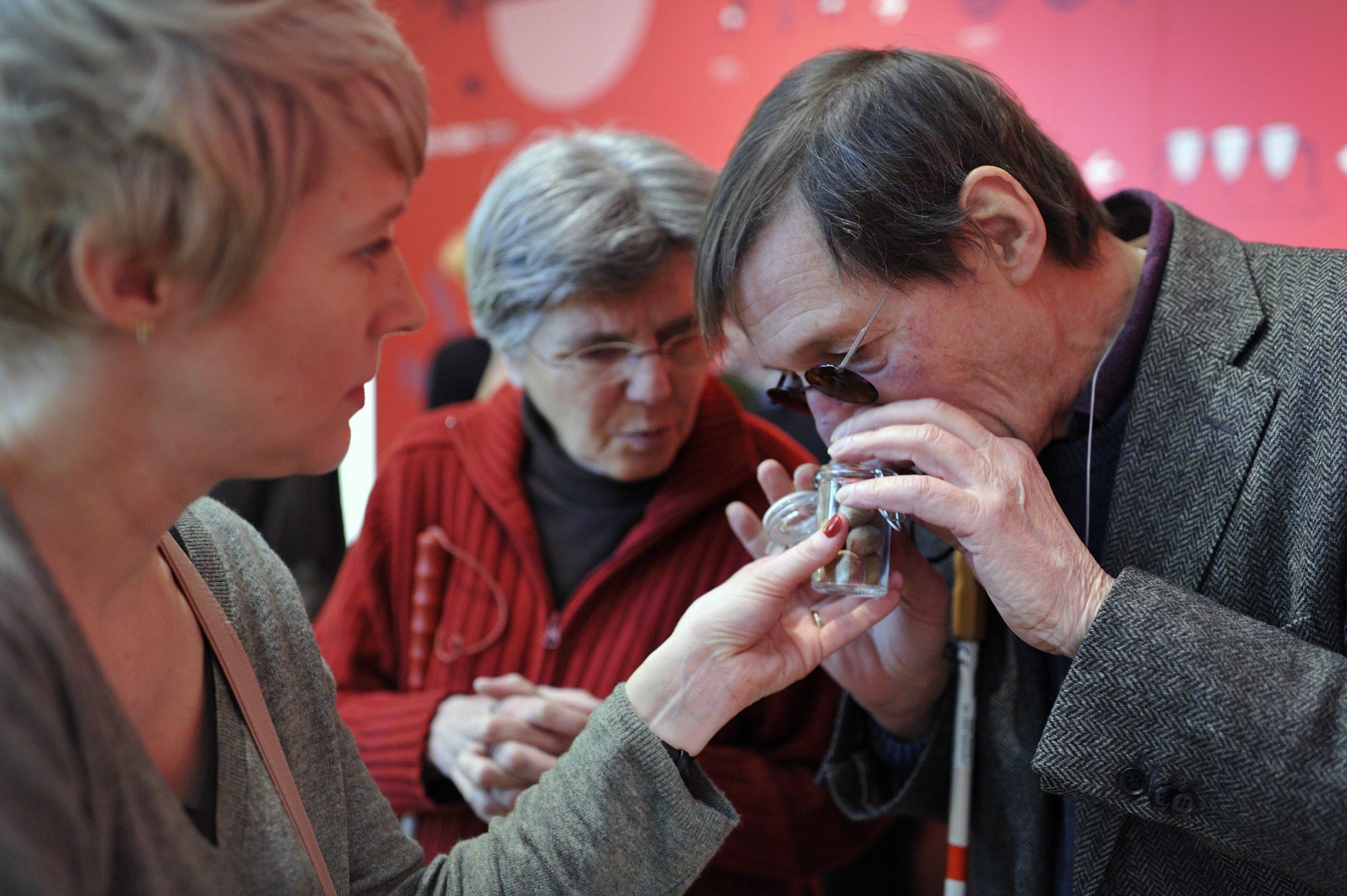 Een man ruikt aan potje dat hem door een dame wordt voorgehouden