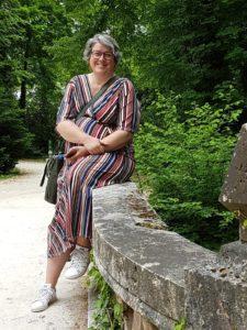 Carla zit zijlings op een stenen muurtje voor een bosrijke achtergrond