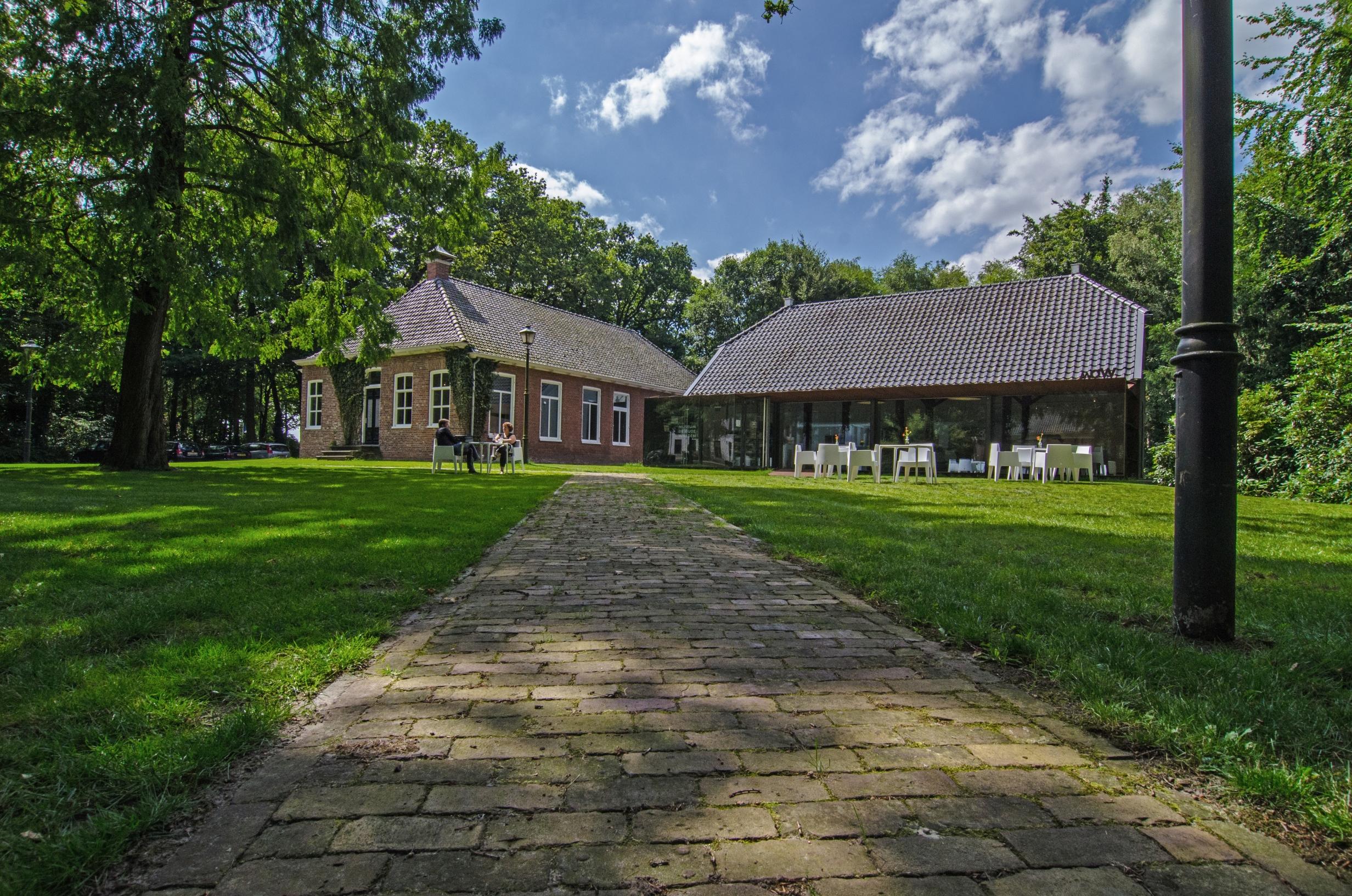 Midden in de natuur tussen de bomen en een groen grasveld ligt aan het eind van een klinkerweg een imposante boerderij waar het museum in is gevestigd.