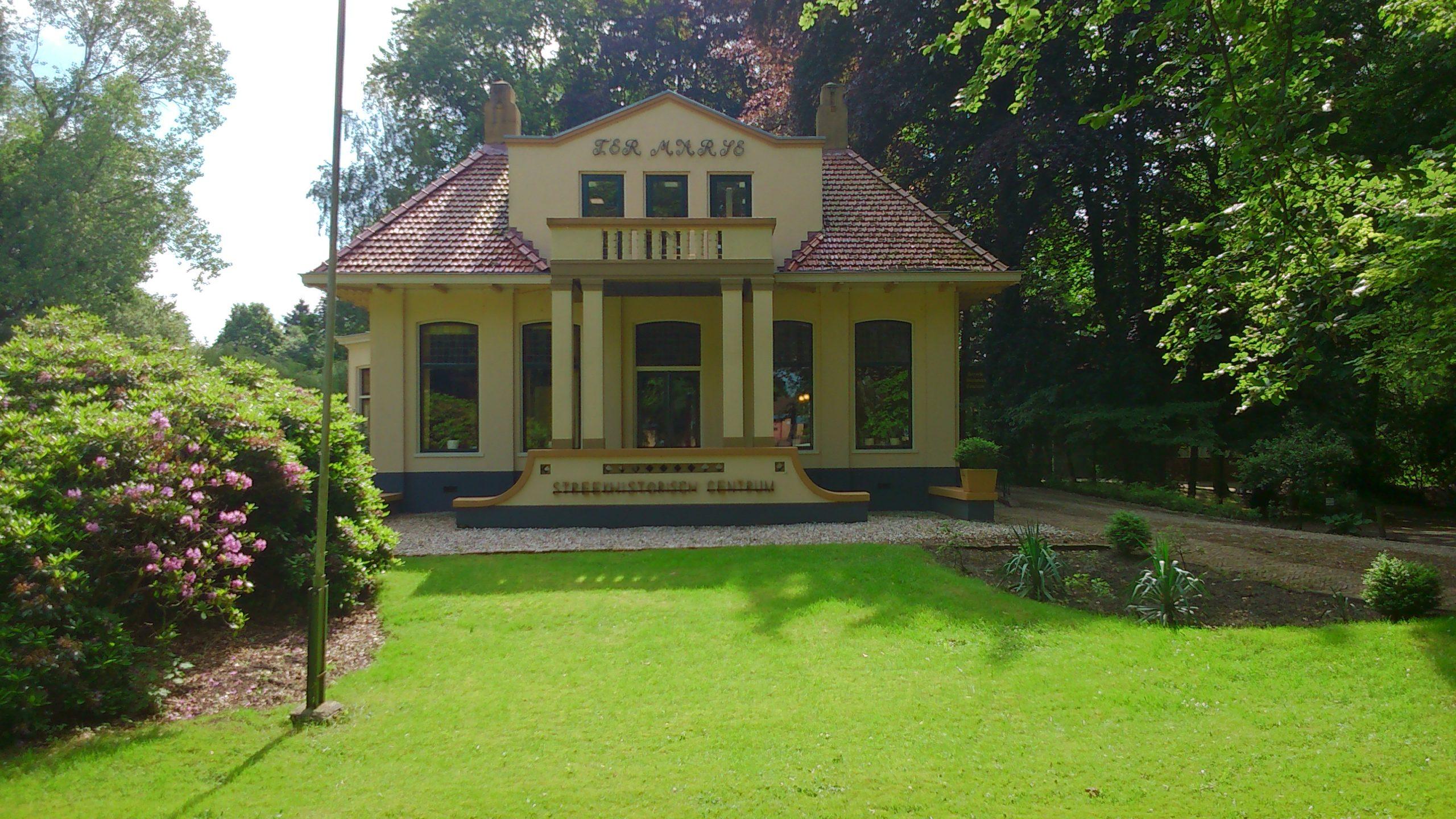 Aan het eind van een groen grasveld, omgeven door bomen, ligt een cremekleurige villa met rood pannendak. Boven de pompeuse ingang met pilaren en een trap ligt een dakkapel met balkon