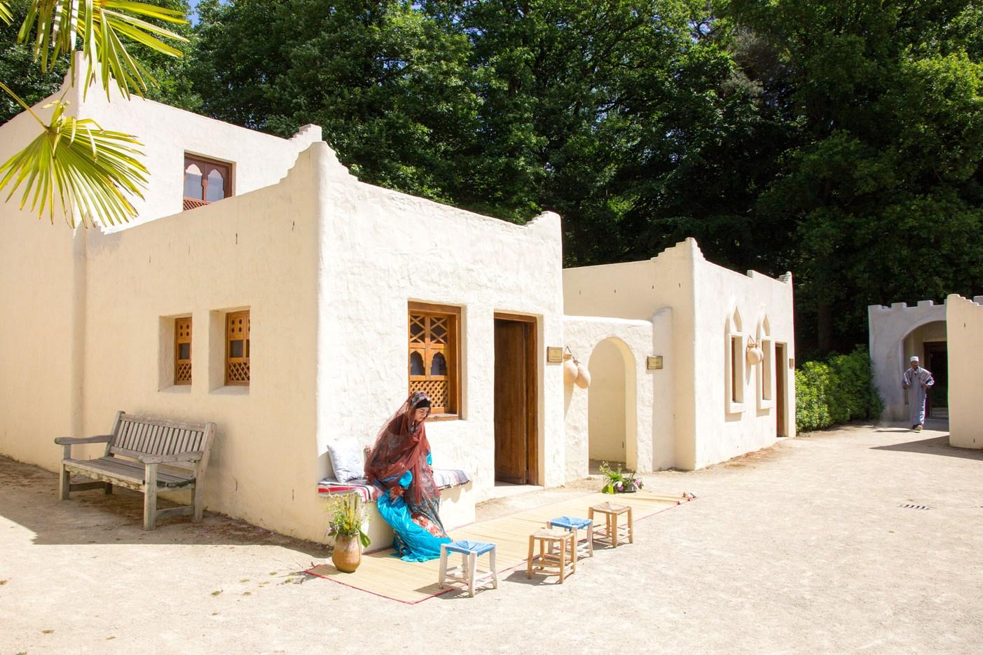 Wit gepleisterde vierkanten huisjes zonder de voor Nederland bekenden puntdaken. Voor een van de huizen zit een gesluierde vrouw bij een aantal krukjes met kleurige kussentjes