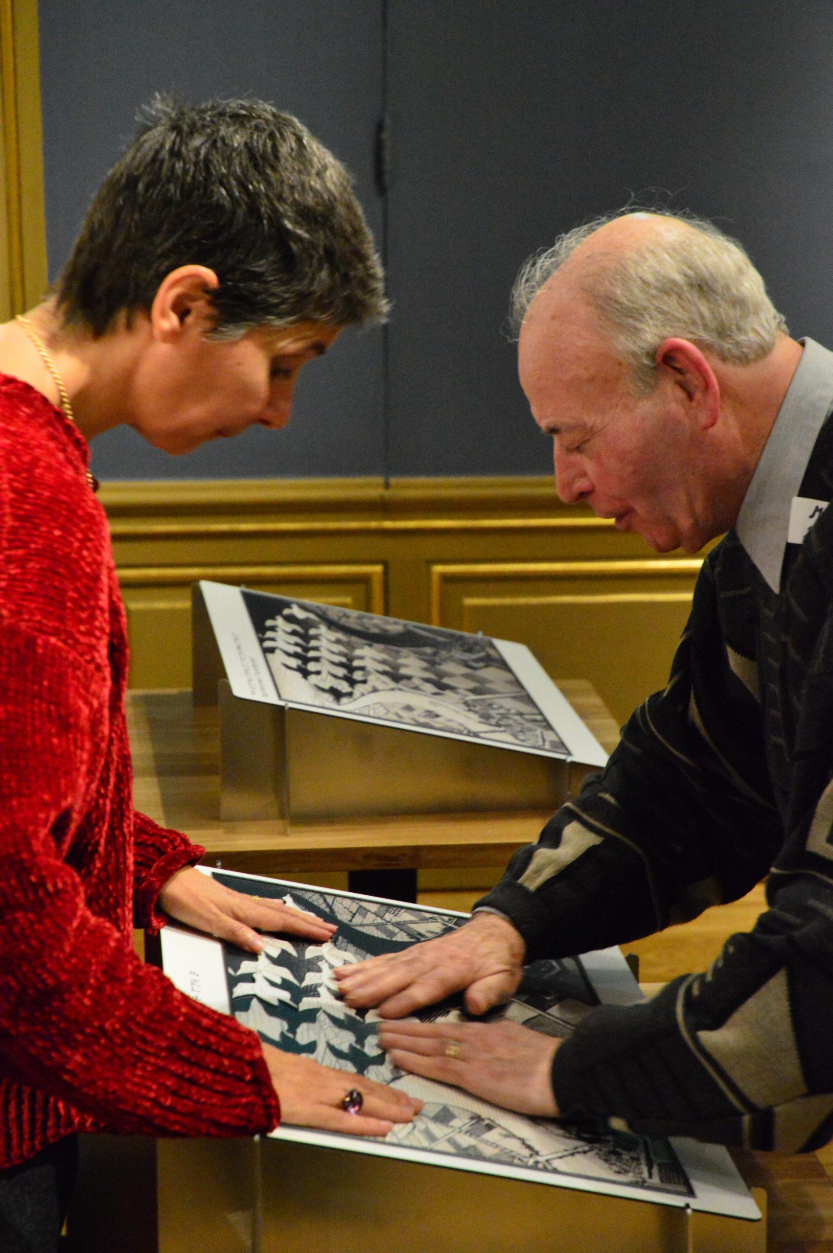 Een man voelt onder begeleiding van een vrouw aan een voelplaat van een tekening van Escher. De tekening is deels in reliëf aangebracht om de techniek uit de kunnen leggen