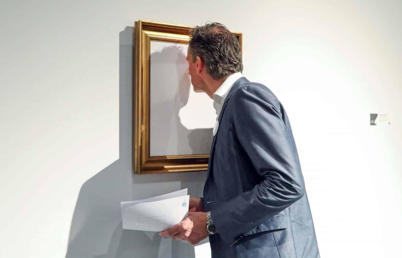 Een man in pak staat voorovergebogen voor een schilderij. Zijn neus raakt het doek bijna. Het schilderij is helemaal wit in een gouden lijst.