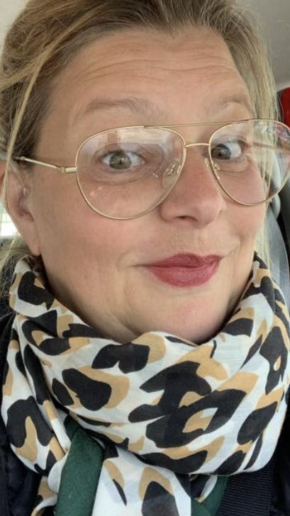 Een vrolijke lachende vrouw met blonde haren en sprankelende bruine ogen