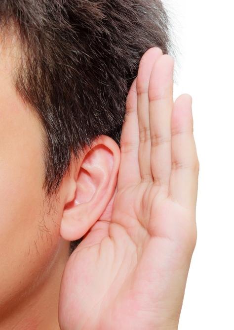 De zijkant van een mannenhoofd met donkerbruin haar. De man houd zijn hand achter zijn oor om het oppervlakte groter te maken zodat hij beter kan horen.