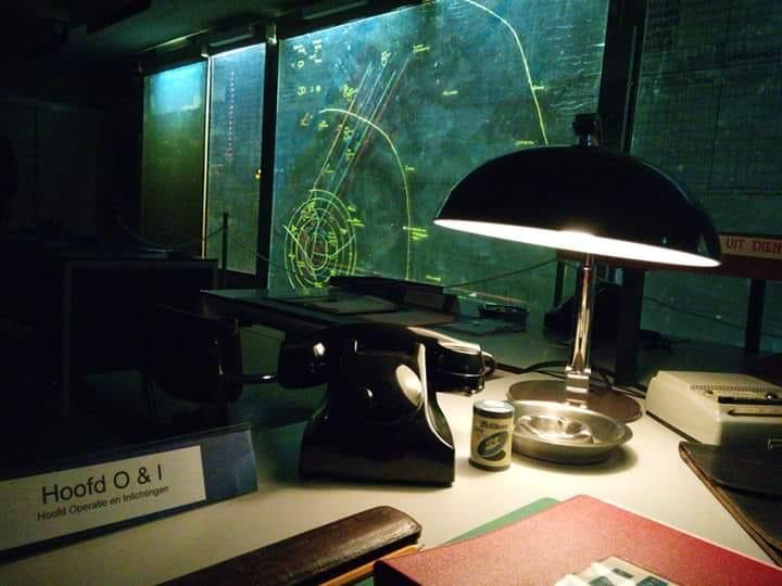 Een bureau met een oude bakelieten telefoon en boeken. Het bureau is schaars verlicht door een enkele bureaulamp