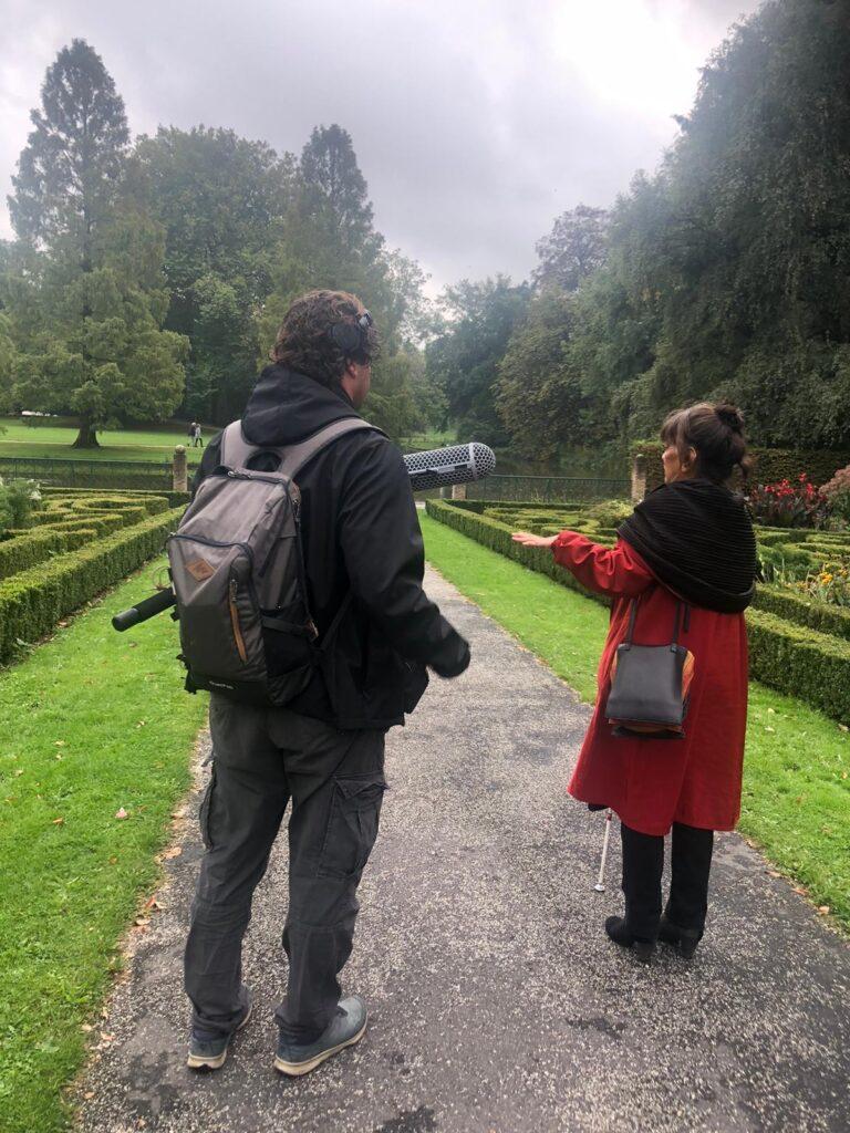 Joan en Edwin staan in het Park en maken opnames voor de audiotour. Joan draagt een rode lange jas met zwarte sjaal en steekt zo mooi af tegen het groen van het gazon en de buxeshagen.