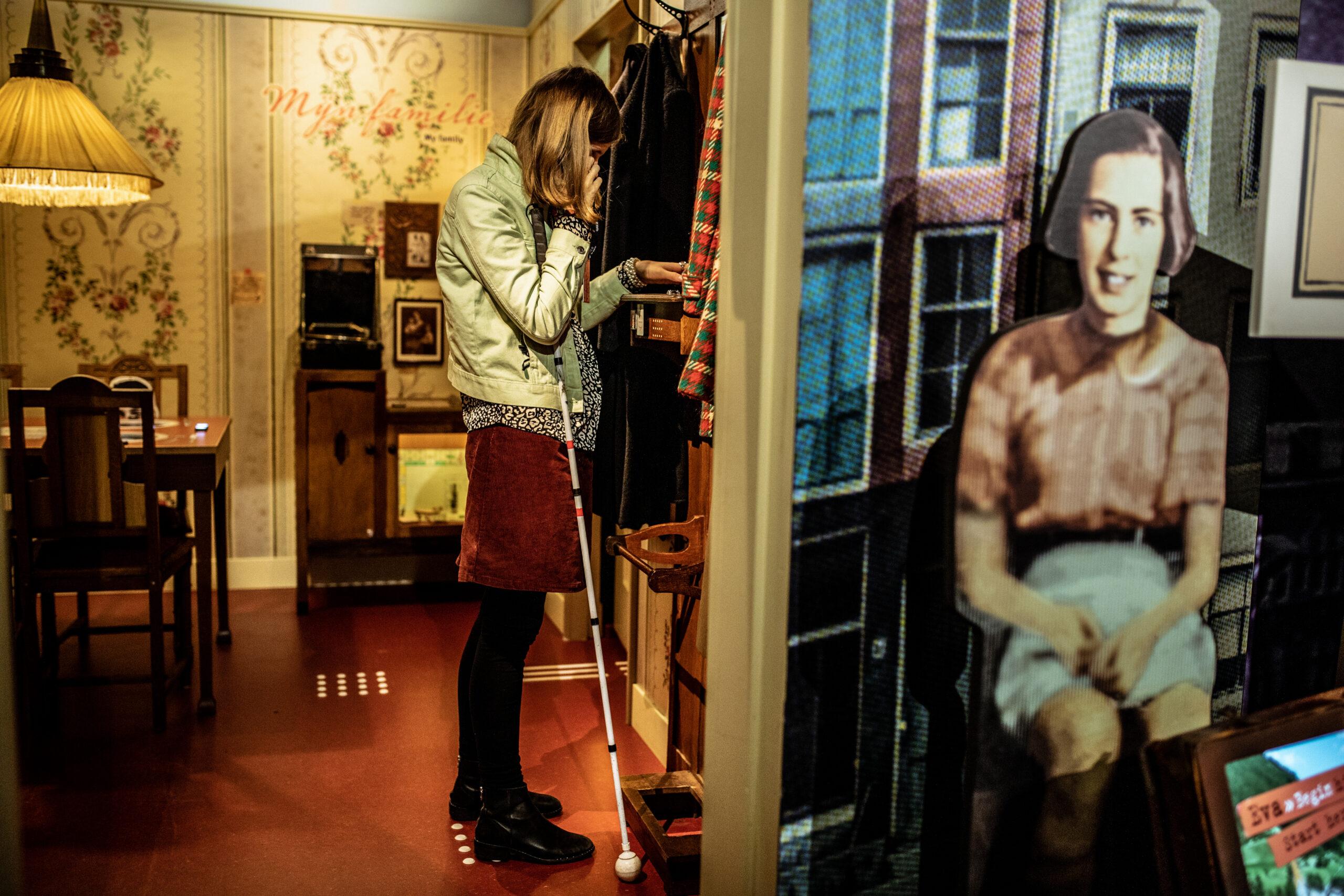 Een meisje staat op een markeringsvlak in de tentoonstelling van het Verzetsmuseum. Zij houdt een podcather aan haar oor waarmee ze naar een beeldbeschrijving luistert. Haar geleide stok rust tegen aan zij.