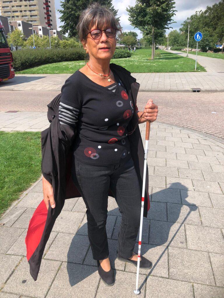 Joan is in het zwart gekleed en heeft haar rode jas nonchalant open geslagen.